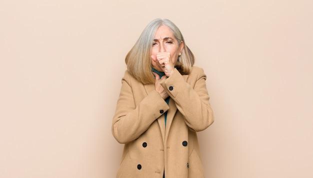 Mulher bonita sênior ou meia idade se sentindo doente com sintomas de dor de garganta e gripe, tosse com a boca coberta