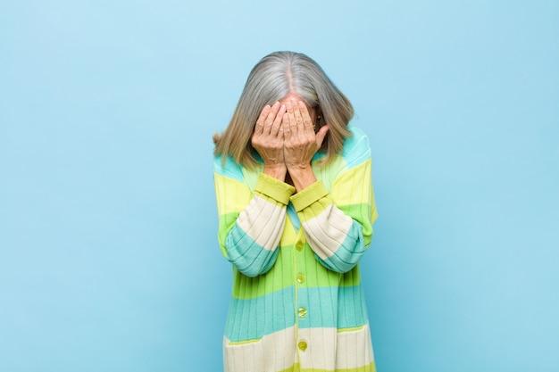 Mulher bonita sênior ou meia idade, sentindo-se triste, frustrado, nervoso e deprimido, cobrindo o rosto com as duas mãos, chorando