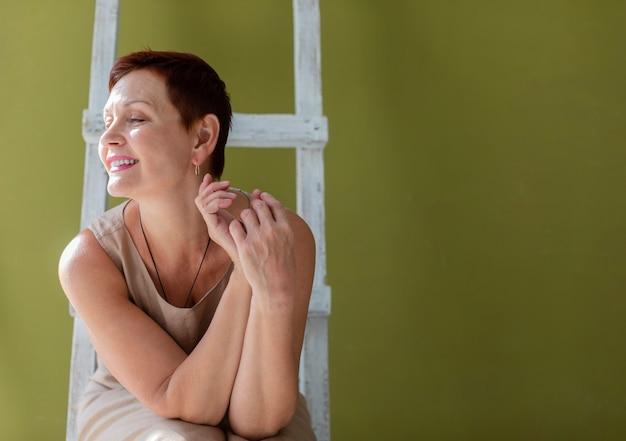 Mulher bonita sênior, sentado em uma escada