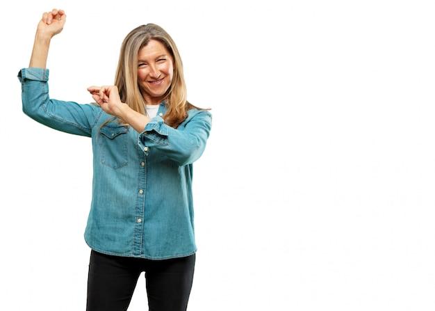 Mulher bonita sênior, sorrindo e dançando a música disco divertido, alegre, olhando feliz e alegre