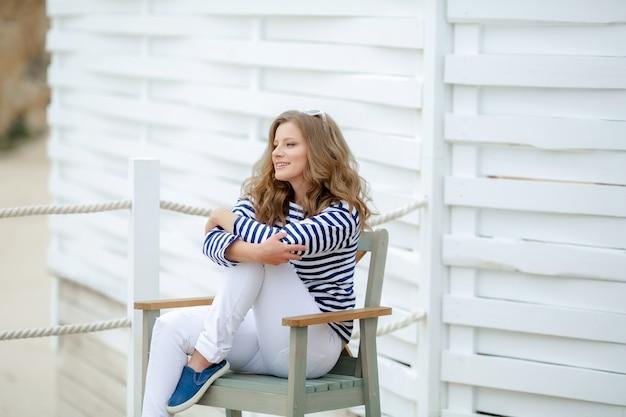 Mulher bonita senta-se em uma cadeira, em roupas masculinas.