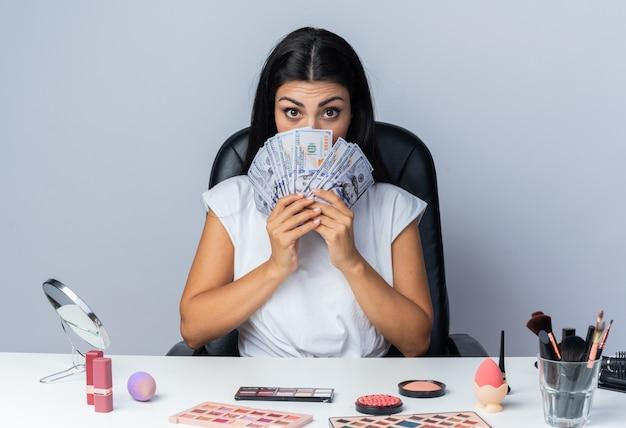 Mulher bonita sentada à mesa com ferramentas de maquiagem e rosto coberto com dinheiro
