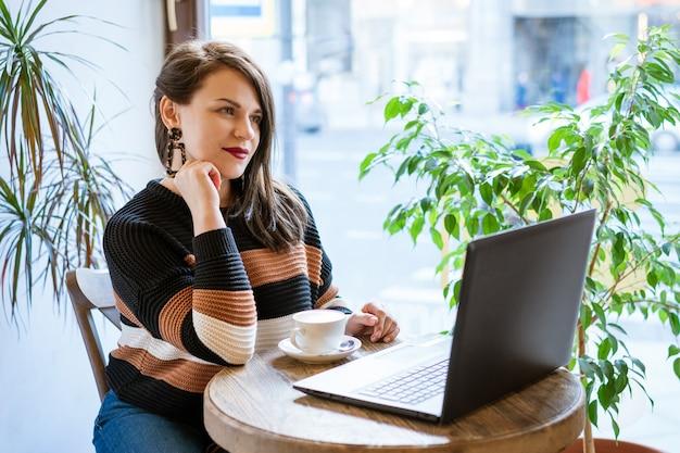 Mulher bonita sentada à mesa em um café com um laptop bebendo café, conceito freelancer