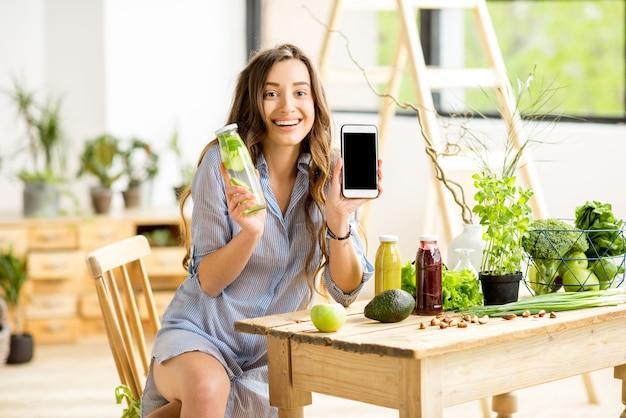 Mulher bonita sentada com bebidas e alimentos verdes saudáveis em casa. conceito de refeição vegana e desintoxicação