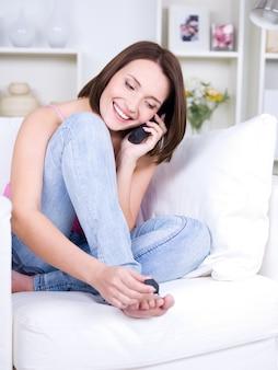 Mulher bonita sentada com o celular fazendo pedicure - dentro de casa