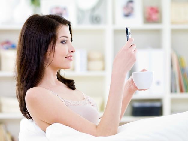 Mulher bonita sentada em casa com copo e celular lendo uma mensagem