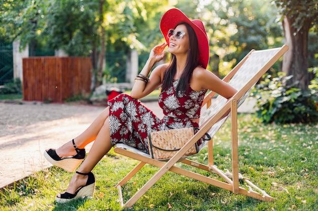 Mulher bonita sentada na espreguiçadeira com roupa tropical. senhora na tendência da moda de verão de estilo de rua. usando bolsa de palha, chapéu vermelho, óculos de sol. menina elegante, sorrindo de bom humor de férias.