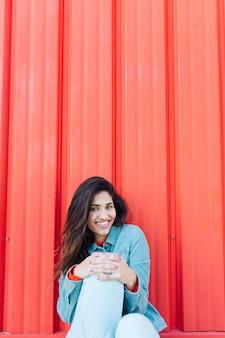 Mulher bonita sentada na frente do fundo vermelho ondulado