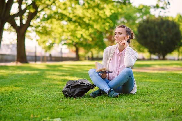 Mulher bonita sentada na grama e lendo o livro no parque no verão