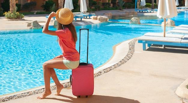 Mulher bonita sentada na mala rosa perto da área da piscina do hotel.