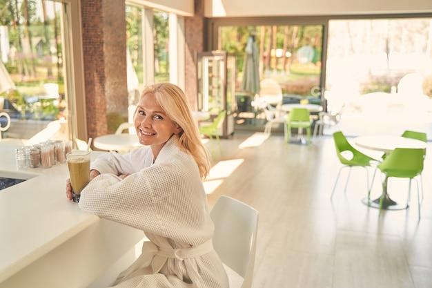 Mulher bonita sentada na mesa branca de um hotel spa enquanto desfruta de um bom dia com uma bebida saborosa