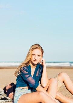 Mulher bonita sentada na praia perto do homem