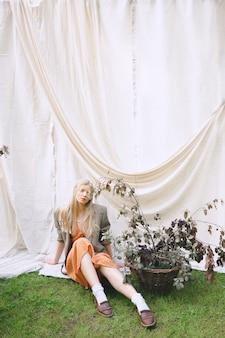 Mulher bonita sentada no chão e olhando no jardim, em vestido laranja e jaqueta durante o dia.