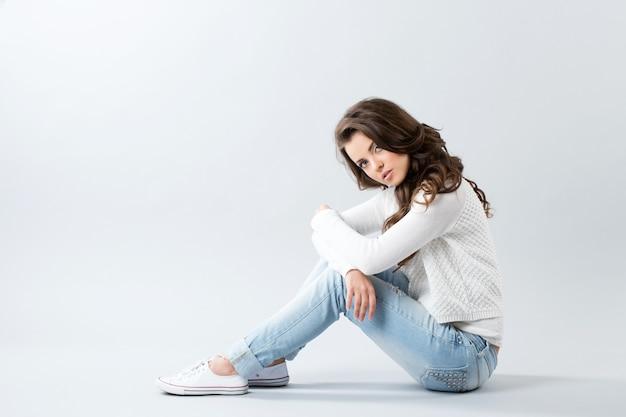 Mulher bonita sentada no chão. garota com cabelo longo ondulado.