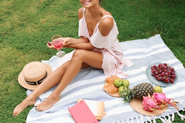 Mulher bonita sentada no cobertor, bebendo vinho e aproveitando o piquenique de verão no jardim tropical.