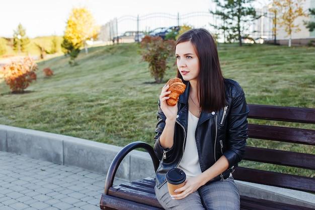 Mulher bonita sentada no parque e comendo croissant