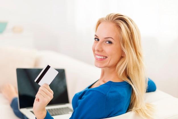 Mulher bonita sentada no sofá com laptop e cartão de crédito