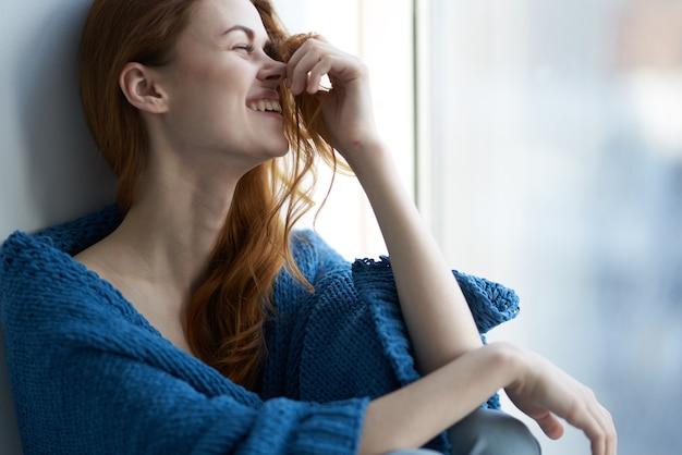 Mulher bonita sentada perto da janela com um descanso xadrez azul