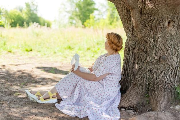 Mulher bonita sentada perto de uma árvore ao ar livre. uma garota romântica em um parque de verão. uma imagem romântica