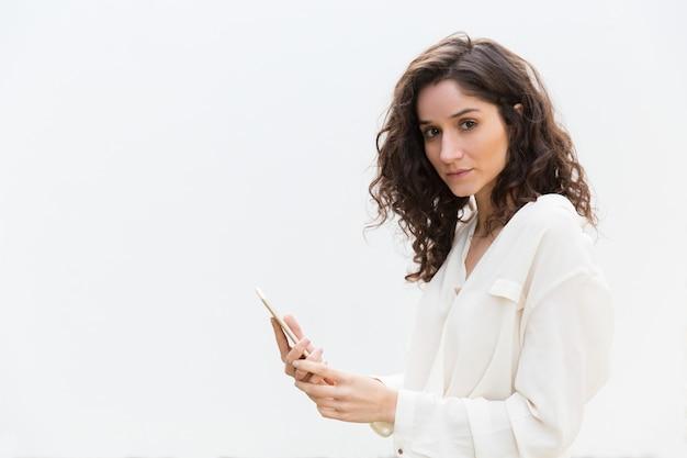 Mulher bonita séria com smartphone olhando