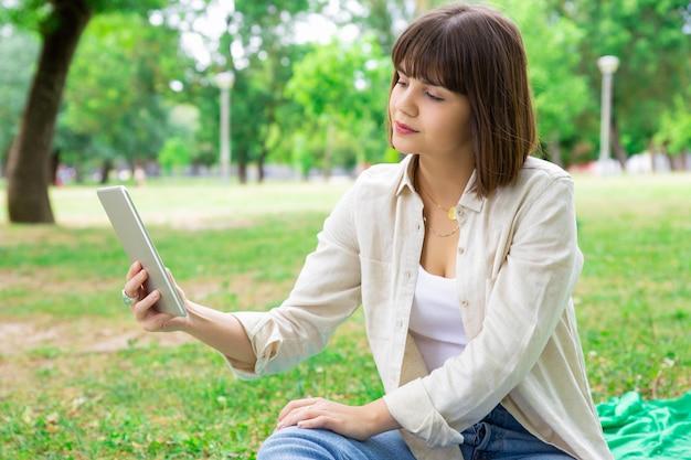 Mulher bonita séria que lê a notícia na tabuleta e que senta-se no gramado