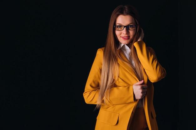 Mulher bonita sexy com cabelo comprido usa óculos e terno amarelo. espaço escuro. olhe para a câmera.