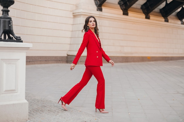 Mulher bonita sexy estilo rico de negócios em um terno vermelho andando na rua da cidade, tendência da moda primavera verão