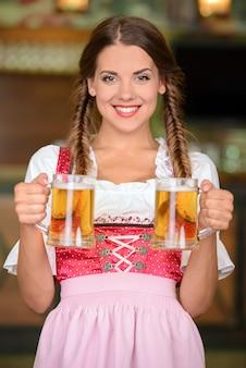 Mulher bonita, sexy garçom segurando copos de cerveja.