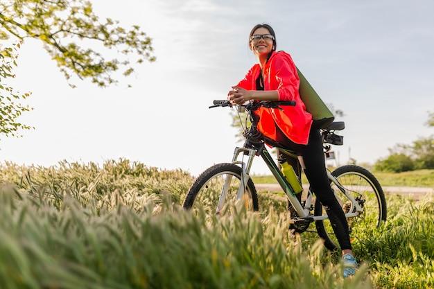 Mulher bonita slim fit praticando esportes de manhã no parque andando de bicicleta com tapete de ioga em roupa colorida de fitness, explorando a natureza, sorrindo, estilo de vida saudável e feliz