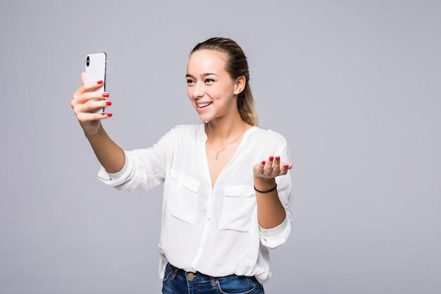 Mulher bonita sociável tirando selfie ou falando em videochamada usando telefone celular isolado sobre parede cinza