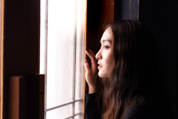 Mulher bonita solitária de retrato. encantadora mulher bonita olhar através da janela