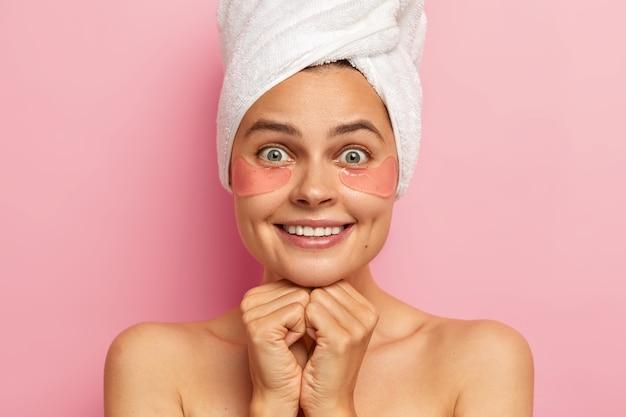Mulher bonita sorri agradavelmente, mostra os dentes brancos, aplica manchas sob os olhos para reduzir as rugas