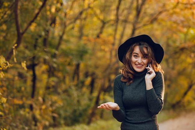 Mulher bonita sorri enquanto fala ao telefone. menina alegre caminha no outono no parque