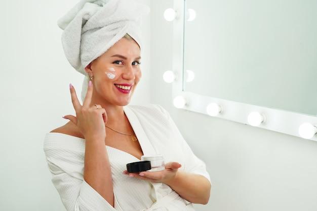 Mulher bonita sorridente aplicar creme para a pele no rosto olhar no espelho do banheiro jovem feliz embrulhar ...