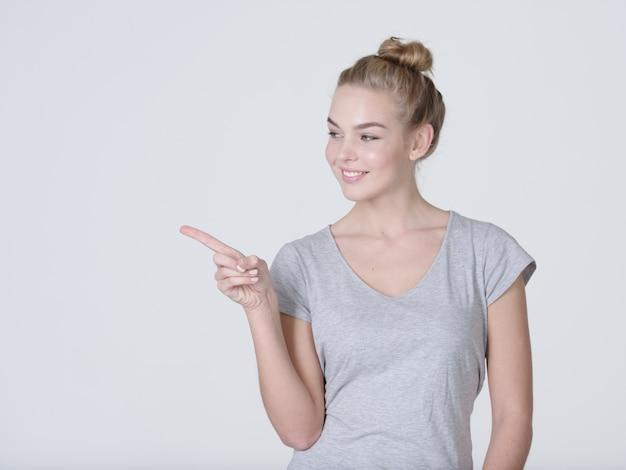 Mulher bonita sorridente, apontando o dedo sobre um fundo cinza. olhando para a câmera
