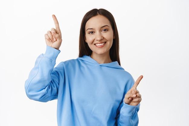 Mulher bonita sorridente apontando para o lado, mostrando duas opções, variantes para clientes, em pé em roupas casuais contra uma parede branca.