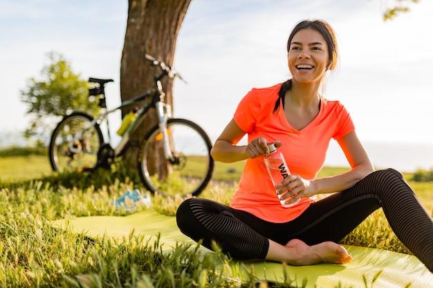 Mulher bonita sorridente bebendo água em garrafa fazendo esportes de manhã no parque