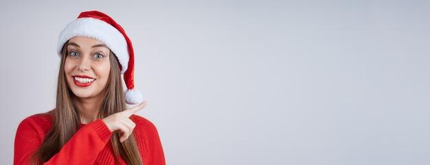 Mulher bonita sorridente com chapéu de papai noel, suéter vermelho, apontando para o lado. banner com espaço de cópia para sua publicidade.