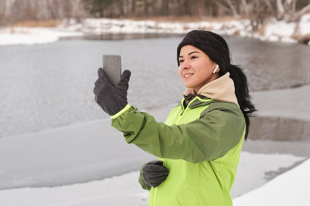 Mulher bonita sorridente com fones de ouvido usando smartpnone enquanto tira uma selfie contra o lago de inverno