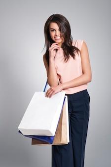 Mulher bonita sorridente com sacolas de compras