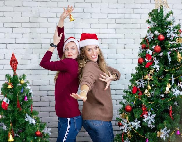 Mulher bonita sorridente dançando ao redor de uma árvore de natal decorada, antes da véspera de ano novo em casa, celebração do feriado de natal Foto Premium