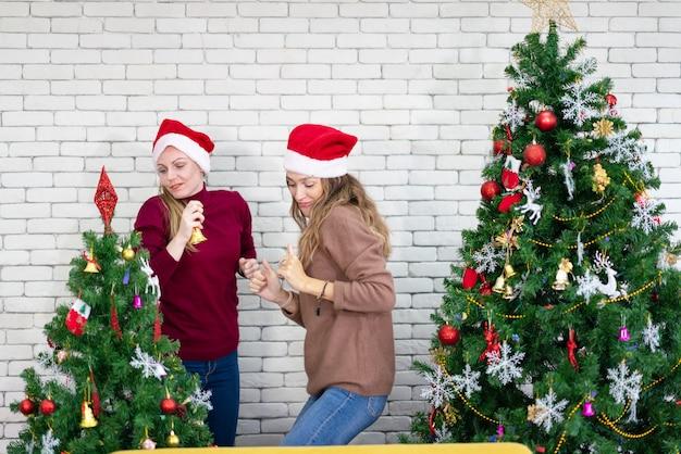 Mulher bonita sorridente dançando ao redor de uma árvore de natal decorada, antes da véspera de ano novo em casa, celebração do feriado de natal