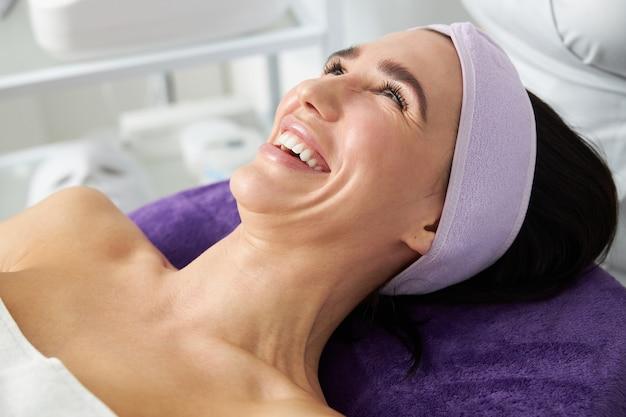Mulher bonita sorridente de cabelos escuros no gabinete de cosmetologia