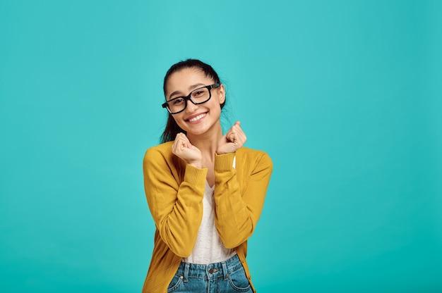 Mulher bonita sorridente de óculos, parede azul, emoção positiva. expressão facial, pessoa do sexo feminino olhando para a câmera no estúdio, conceito emocional, sentimentos
