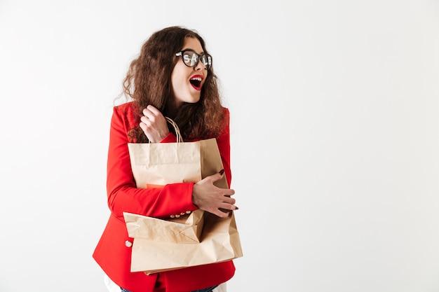 Mulher bonita sorridente de venda segurando sacolas de papel