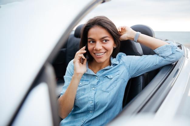 Mulher bonita sorridente, dirigindo um carro e falando no celular