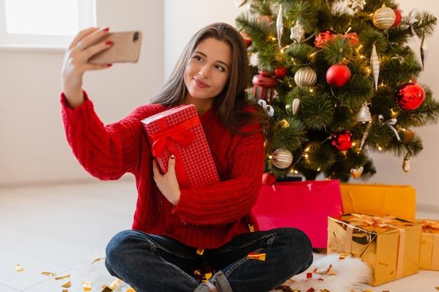 Mulher bonita sorridente e animada com um suéter vermelho sentada em casa na árvore de natal desempacotando presentes e caixas de presente tirando uma foto de selfie na câmera do telefone