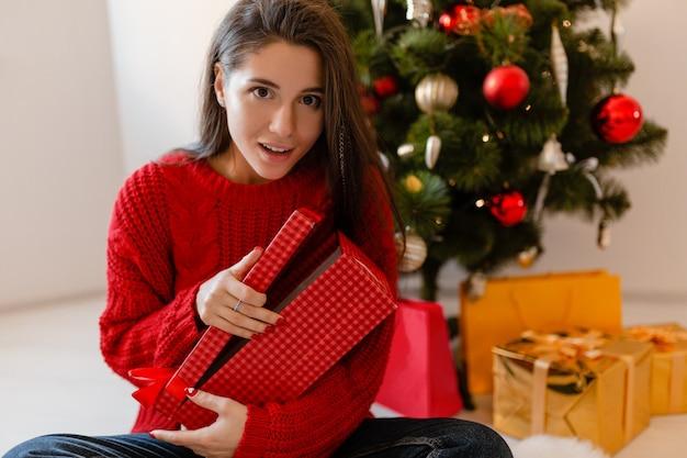Mulher bonita sorridente e animada com um suéter vermelho sentada em casa na árvore de natal desempacotando presentes e caixas de presente