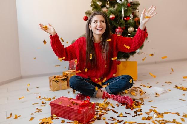 Mulher bonita sorridente e animada com um suéter vermelho sentada em casa na árvore de natal jogando confetes dourados cercados de presentes e caixas de presente