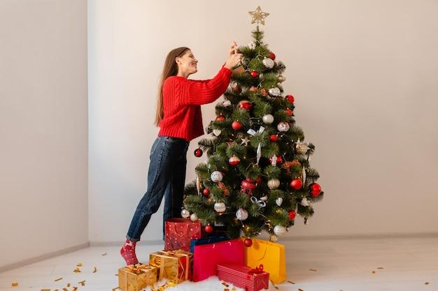 Mulher bonita sorridente e animada em um suéter vermelho em pé em casa decorando uma árvore de natal cercada de presentes e caixas de presente